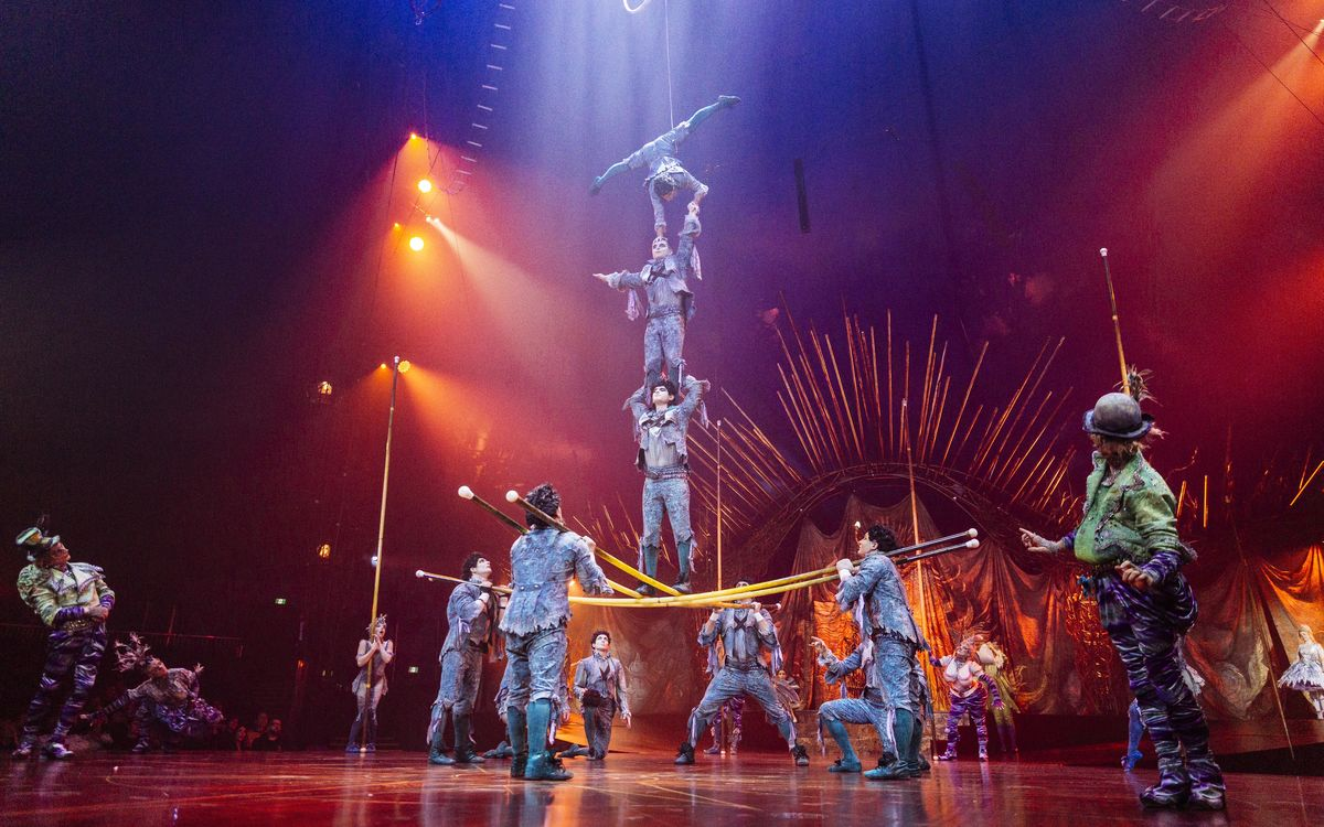 Cirque du Soleil acrobats stand upon each others shoulders during a performance.