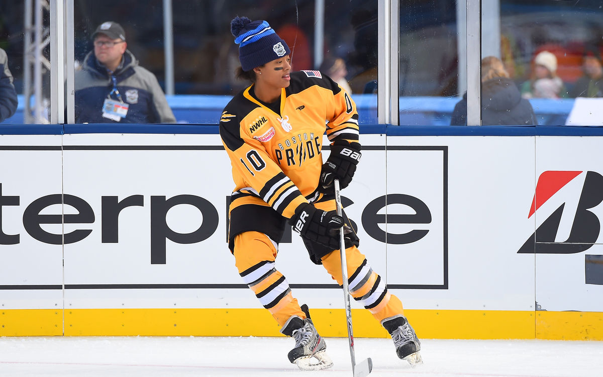 Blake Bolden skates on the ice in her yellow NWHL jersey.