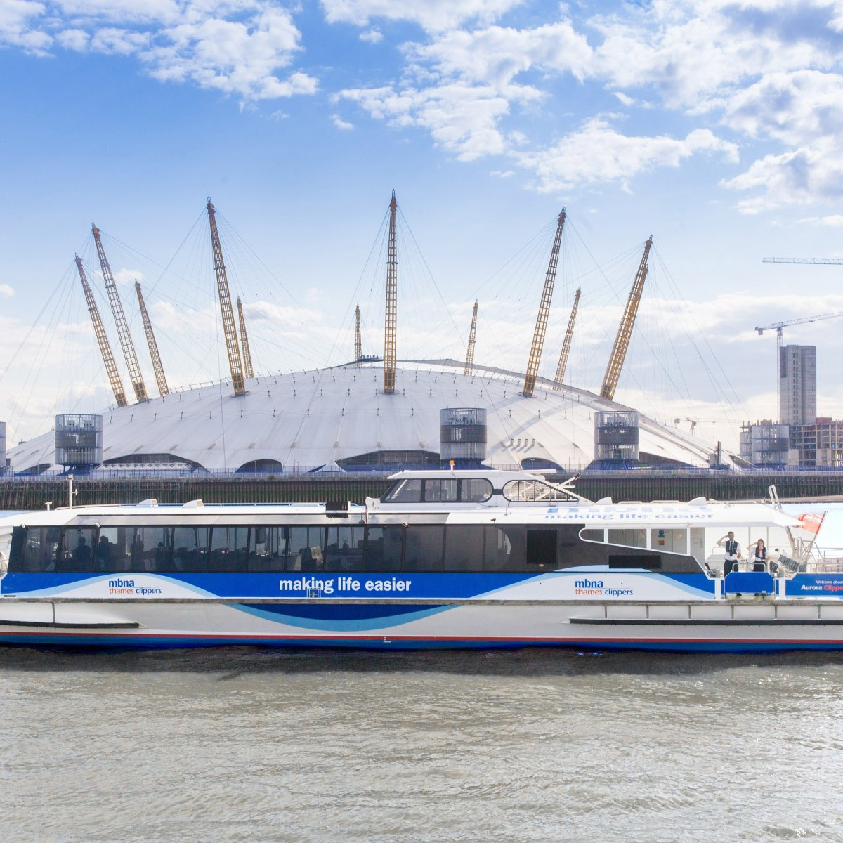 Exterior image of the MBNA Thames Clipper on the water with The O2 in the background