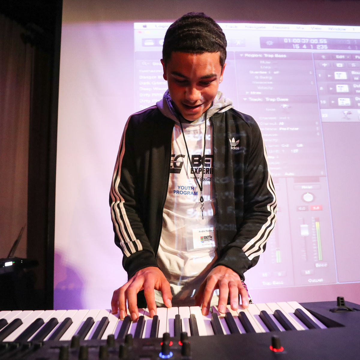 A student wearing an AEG and BET shirt plays the keyboard during a music production class.