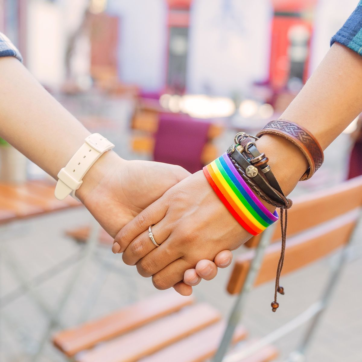 Two women hold hands - one wearing a Pride rainbow bracelet.