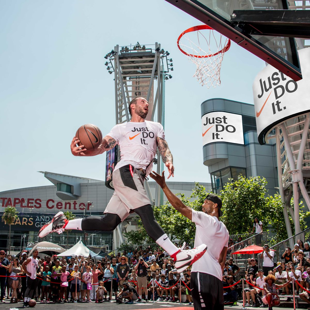A man is mid jump during his slam dunk attempt at the Nike Basketball Slam Dunk Contest at L.A. LIVE