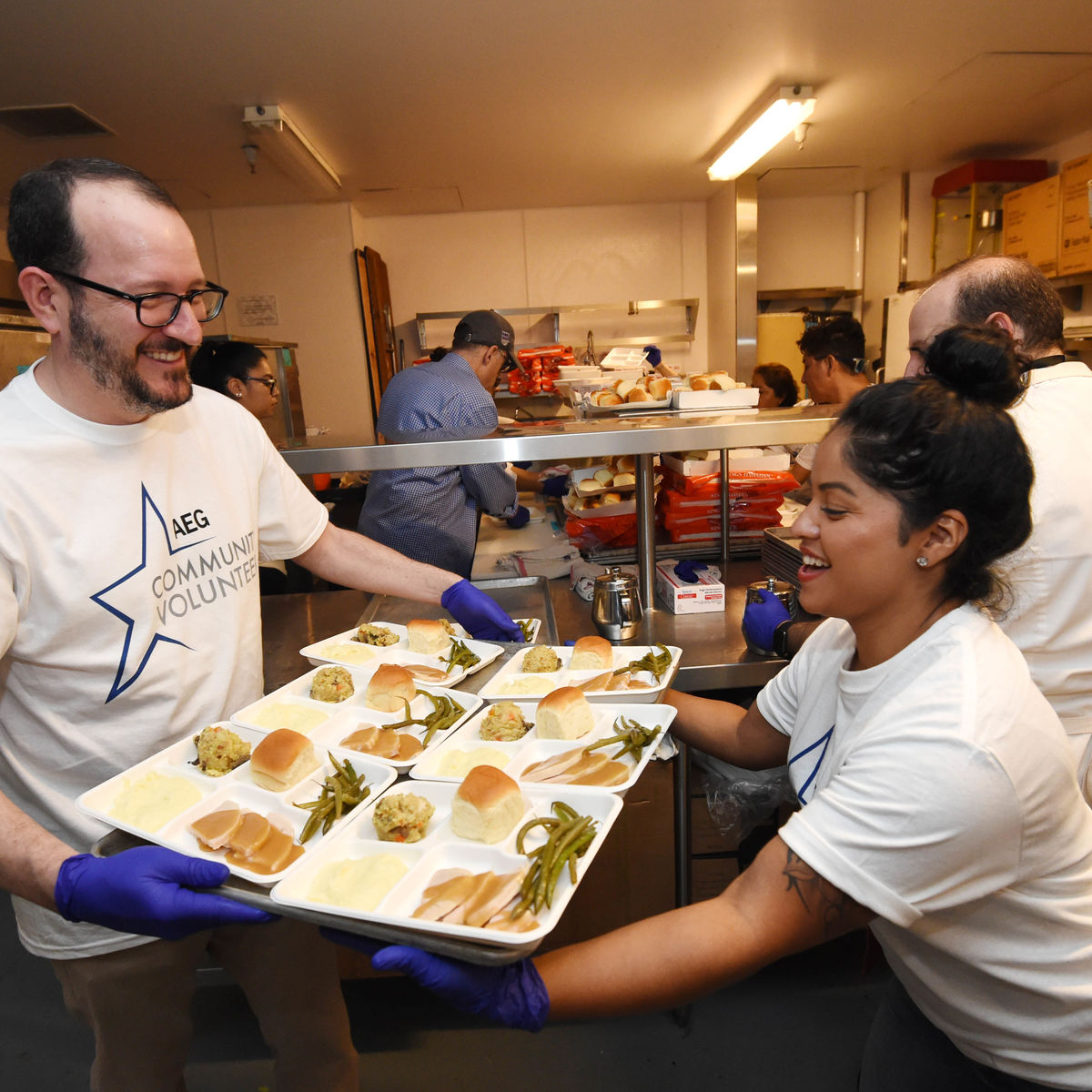 AEG CEO & President Dan Beckerman hands a tray of prepared Thanksgiving meals to another volunteer in the kitchen at The Novo at L.A. LIVE.