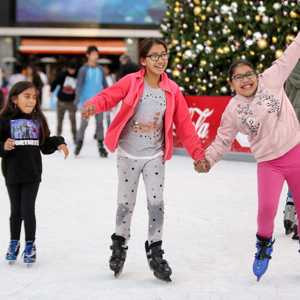 Three girls ice hold hands and smile as they ice skate.
