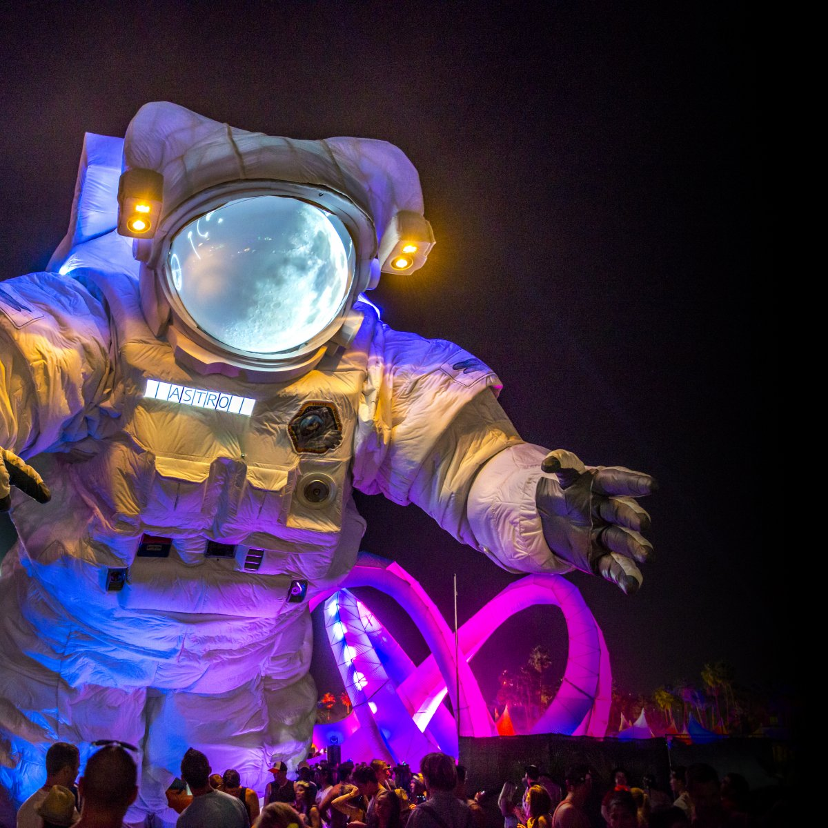 Image of a large astronaut art installation with a ferris wheel in the background during night time