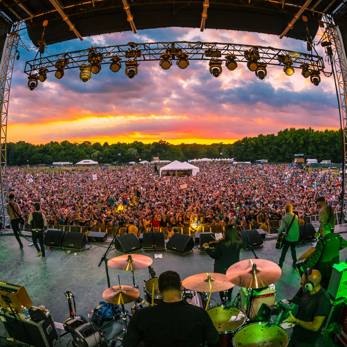 Image looking out into the crowd from behind performers on stage with a vibrant sunset at Firefly Music Festival