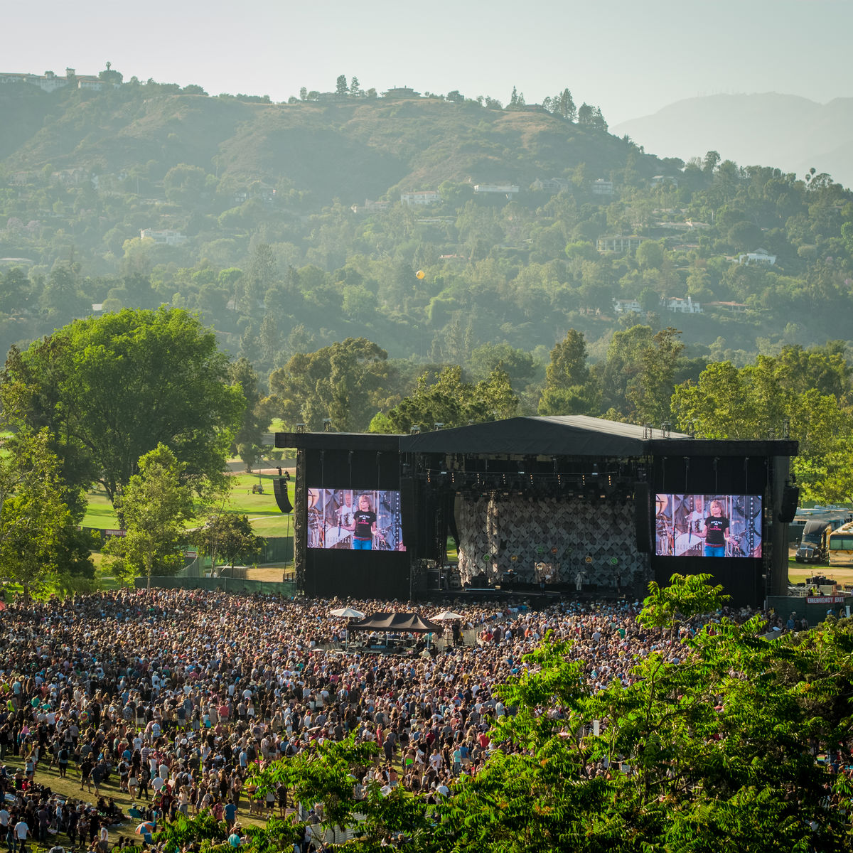 Image of stage and crowd from a distance with trees and hills in background